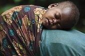 Pygmy Baaka child asleep on her mother Cameroon