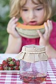 Girl watching Wasps trapped ; Wasps are trapped in a glass jar filled with syrup tabletop garden with fruit (melon and strawberries). The girl is four years old