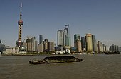 Barges loaded with coal and modern Shanghai in China