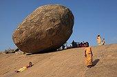 Children playing slide in Mamallapuram India ; This rock is called the ball of butter of Krishna Mamallapuram