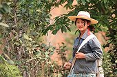 Masked woman picking tea in Burma