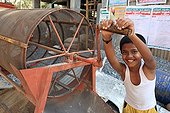 Smiling boy turning the crank of a sieve India
