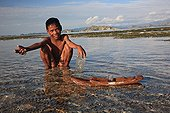 Boy playing with a boat Messah Pulau Flores Indonesia