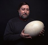 Man carrying an Elephant bird Egg ; Volume of the egg, eight liters<br>Character: Jacques Maigret