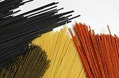 Spaghettis de différentes saveurs et couleurs sur fond blanc ; jaune : semoule de blé dur. rouge : tomate et quinoa. vert : quinoa ail et persil. noir : semoule de blé à l'encre de sèche
