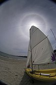 Sailboat in front of the Sun and its halo of 22 ° radius