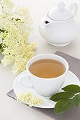 Elderflower and elderberry herbal tea in a white cup