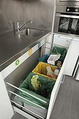 Separation of waste in a modern apartment Barcelona ; Different bins for organic waste, plastic, cardboard, glass