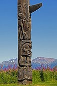 Detail of Totem old Gitksan Nation in Canada ; Representation of a human being crying, topped by a stylized orca indicate membership in the clan of the killer.