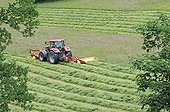 Tractor mowing a meadow in spring Doubs France