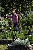 Young girl with fork-spade in an aromatic plants garden