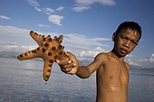 Boy and Starfish Messah Pulau Flores Indonesia