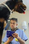 Vérification du passeport d'un chien par un vétérinaire ; Le passeport canin est un document officiel européen qui permet de centraliser et d'harmoniser la certification de documents officiels sanitaires en particulier la vaccination contre la rage canine. Toute délivrance d'un passeport suppose l'identification du carnivore domestique.<br>