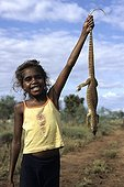 Aborginal girl holding an hunted sand monitor in Australia ; Warlpiri Aborginal community of Alice Spring