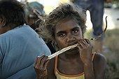 Aborginal girl eating a sand monitor in Australia ; Warlpiri Aborginal community of Alice Spring
