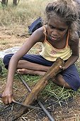 Aboriginal girl cooking a kangaroo tail in Australia ; Warlpiri Aborginal community of Alice Spring