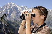 Boy looking through binoculars in the Alps France