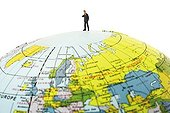 Business executive on top of a globe