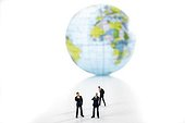 Three business executives in front of a globe