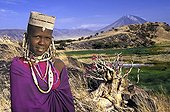 Maasai girl in traditional dress in front of Lengai Mount