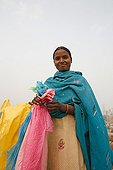 Woman with plastic bags for recycling India ; After being collected in the streets of Delhi used bags are sorted by color before processing your luggage and other fashion accessories or decoration.