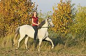 Young horse rider without a saddle toelting on a Paso Fino horse in autumn in the evening