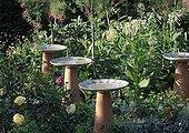 Bowls in a flowered garden ; Landscapers: Ossart-Maurières<br>Bowls: Rachid Koraïchi