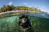 Diver on the beach of the resort Harbour Village in Bonaire