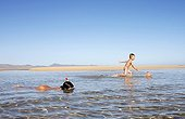 Boy, 4 years, trying to catch fish with a net, girl, 8 years, making first attempts at snorkeling in shallow water, on the beach of Fuerteventura, Canary Island, Spain, Europe