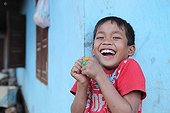 Portrait of a child laughing while eating a candy in Laos