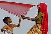 Mother and son drying a red sari, Ram Devra, near Pokaran, Rajasthan, North India, Asia