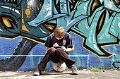 Ten-year-old boy playing with his Nintendo in front of a graffiti wall, Germany, Europe