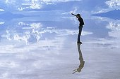 Young woman reflecting on the surface of the flooded salt desert Salar de Uyuni, Bolivia