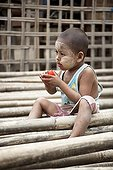 Child playing in a stock of Bamboo in Burma