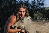 Olivier Houalet with a female warthog in Namibia ; He runs a rehabilitation center for felines before their reintroduction in the wild.