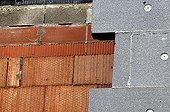 Construction d'un éco-quartier à Walbach dans le Haut-Rhin ; Pose de l'isolation extérieure sur des murs en briques isolantes Monomur. Bâtiment Basse consommation.