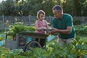 Gardener and little girl in a kitchen garden