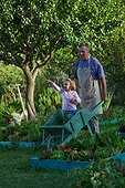 Gardener and little girl in a kichen garden