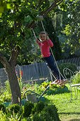Little girl playing on a swing in a garden