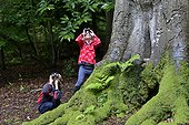Young boy and girl bird watching in woodland in summer UK