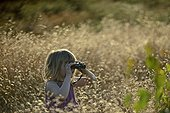 Young girl bird watching in meadow in summer UK