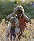 Young boy and girl bird watching in meadow in summer UK