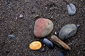 Rounded pebbles by the sea on a black sand beach