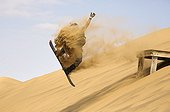 sandboarding in the dunes of the Namib Desert Namibia ; just outside of the coastal town of Swakopmund.