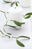 Mistletoe and candle on a table