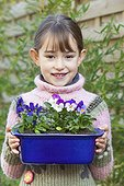 Little girl and pansies in pot in a garden