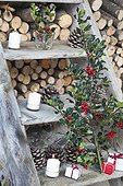 holly and candles on a ladder in a garden