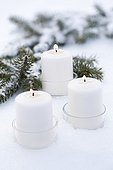Candles and spruce branche in the snow