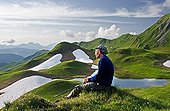 Man sitting on top of the Cormet Arèches Alpes France ; Character: Patrice Labarbe<br>Massive Beaufortin