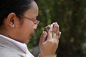 Femme faisant un voeu avant de relâcher un oiseau au Wat ; Pagode bouddhiste de Wat Phnom Daun Penh